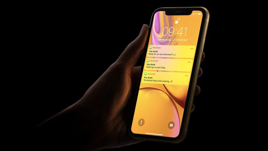 iPhone XR yellow in hand black background press image
