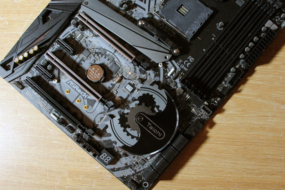 A top-down view of the ASRock X470 Taichi motherboard, showing off the cog-shaped heatsink.