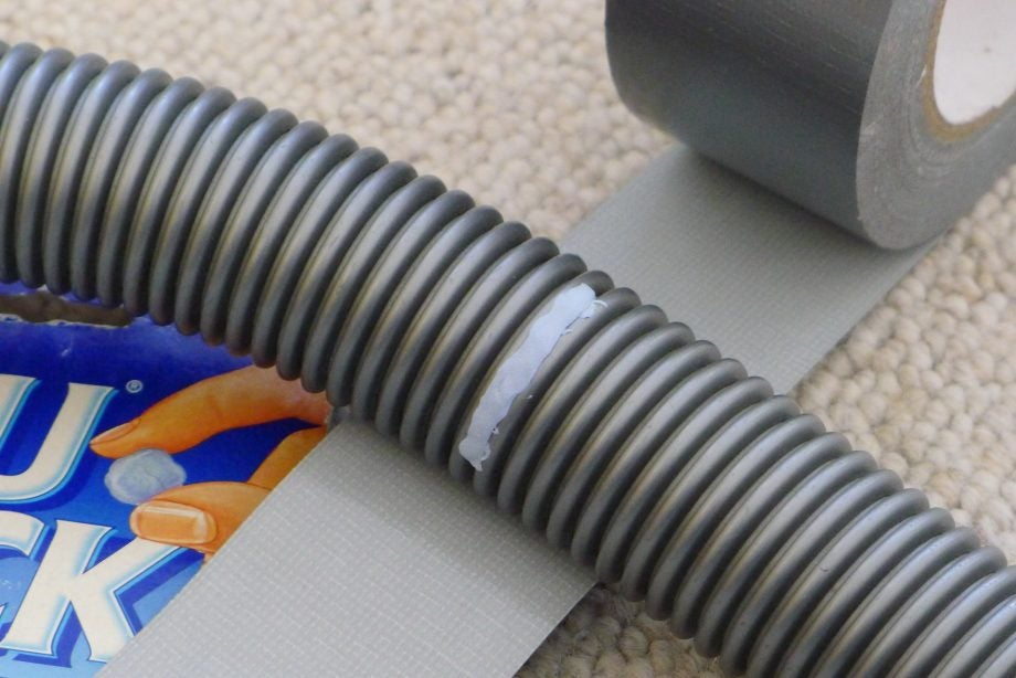 Patching a vacuum hose with Blu Tak and masking tape