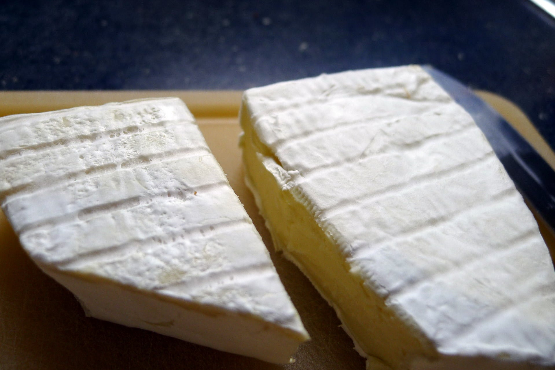 Two blocks of brie, one previously frozen, one fresh. The rind on the frozen one is darker and looks patchy.