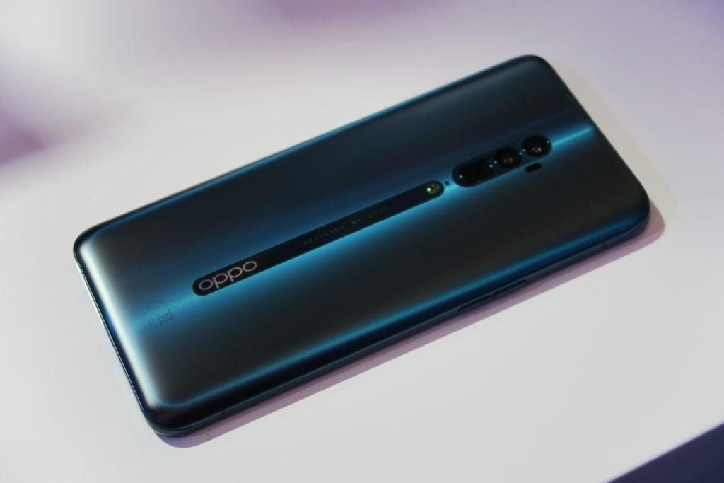 Oppo Reno 10x Zoom hands on table central reflection angled