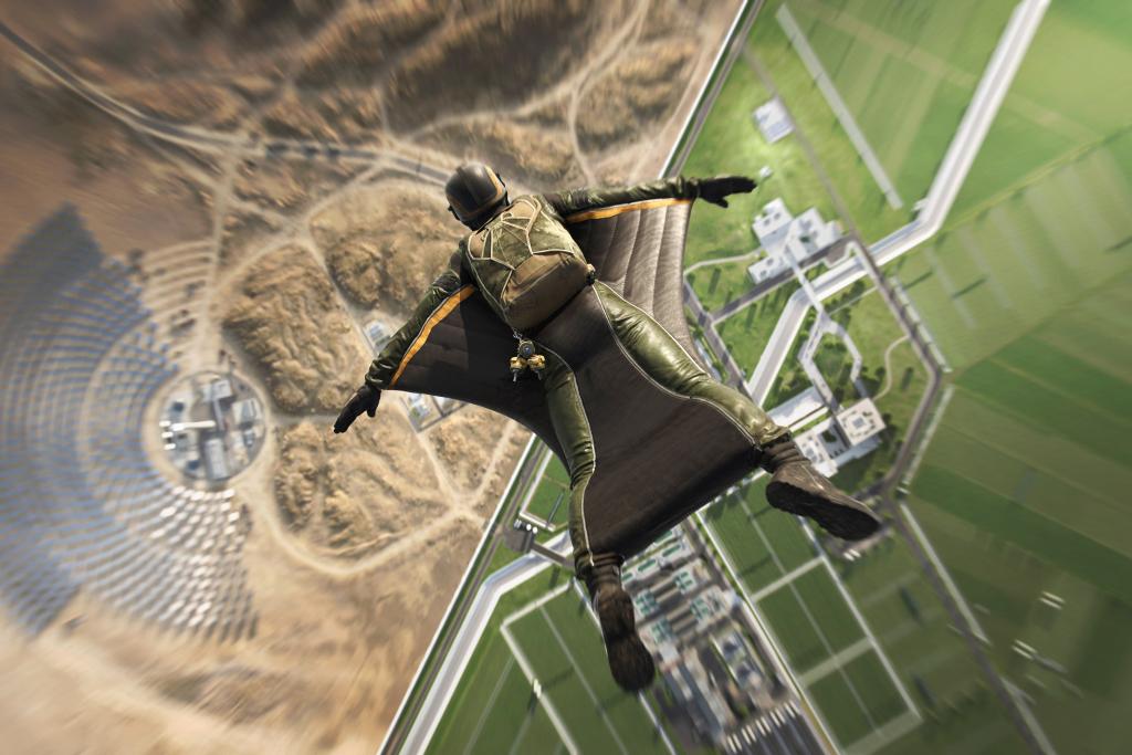 Man in wingsuit flying down to desert