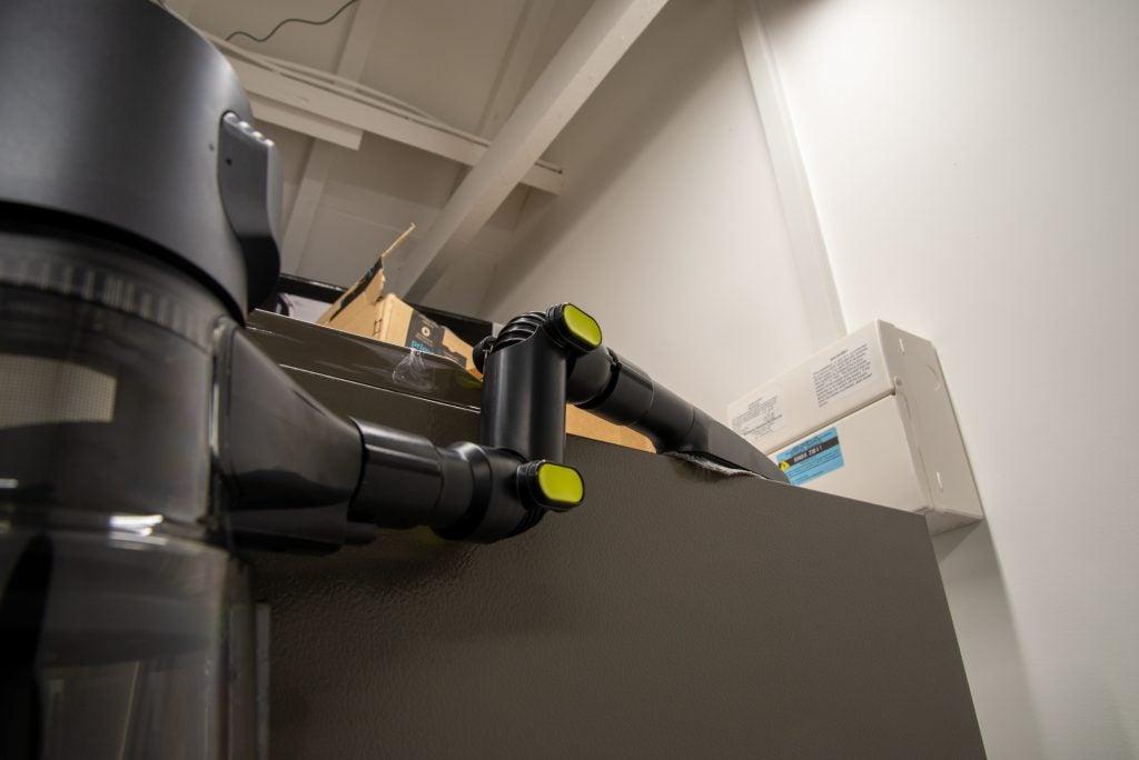 Beko PowerClean Cordless Vacuum Cleaner VRT94929VI cleaning on top of a fridge