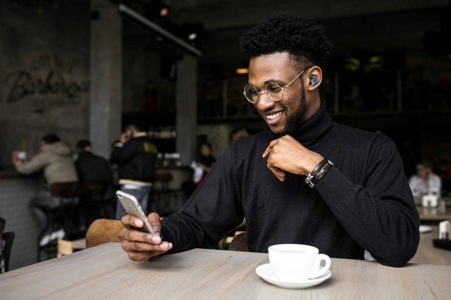 Man in cafe wearing Cleer Ally Plus II earbuds