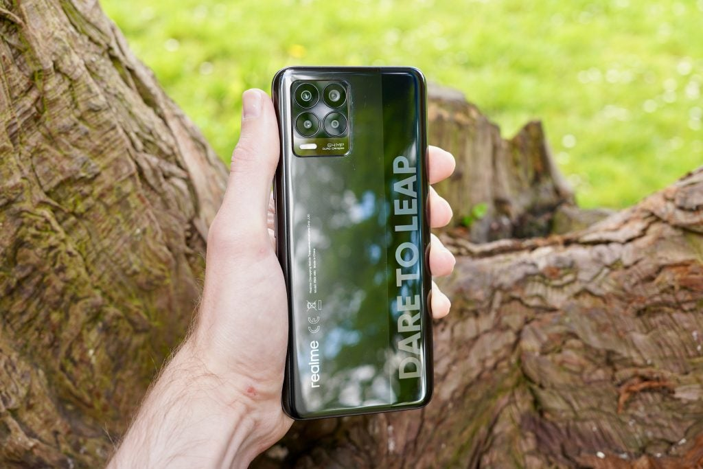 Realme 8 being held showing the back
