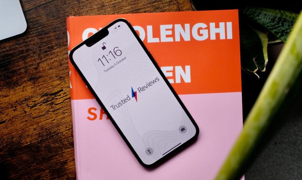 Imagen frontal del iPhone 13 pro con fondo de pantalla TR